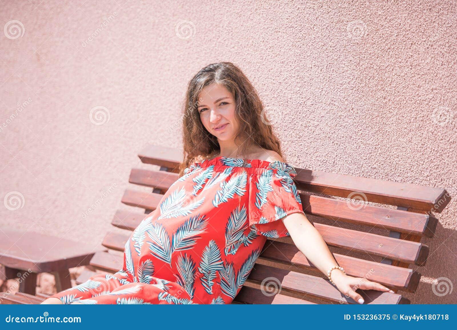 Een zwanger meisje zit op een bank Plaats voor de inschrijving Mooi zwanger meisje in kleding