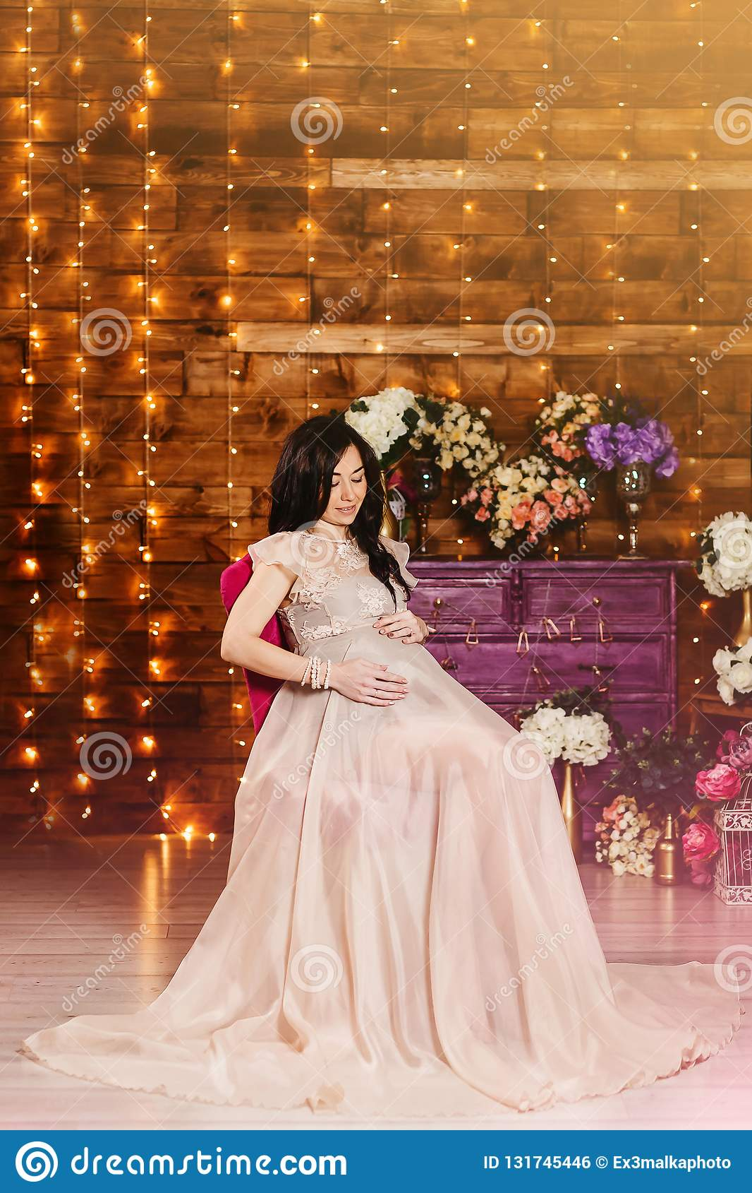 Een zwangere vrouw in een mooie lange toga in studio