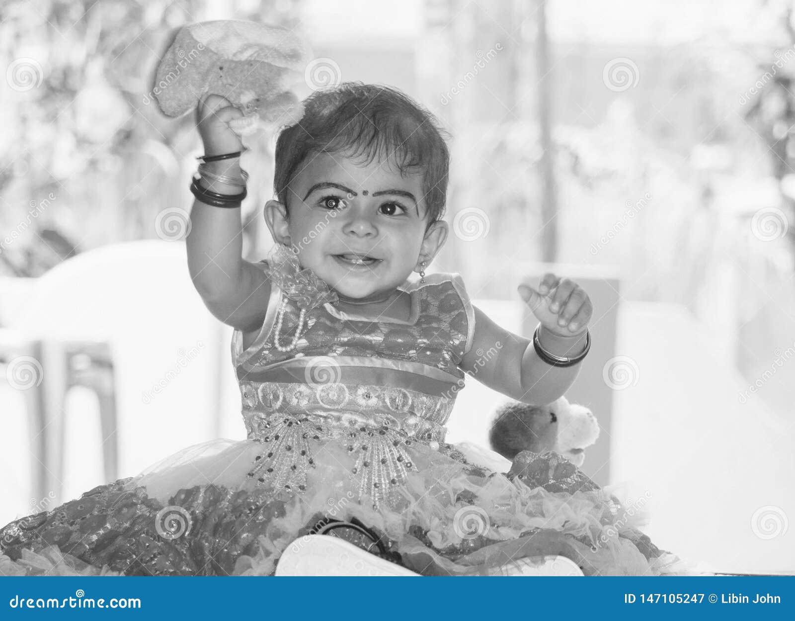 Een zwart-wit portret van een glimlachend leuk Indisch kindmeisje