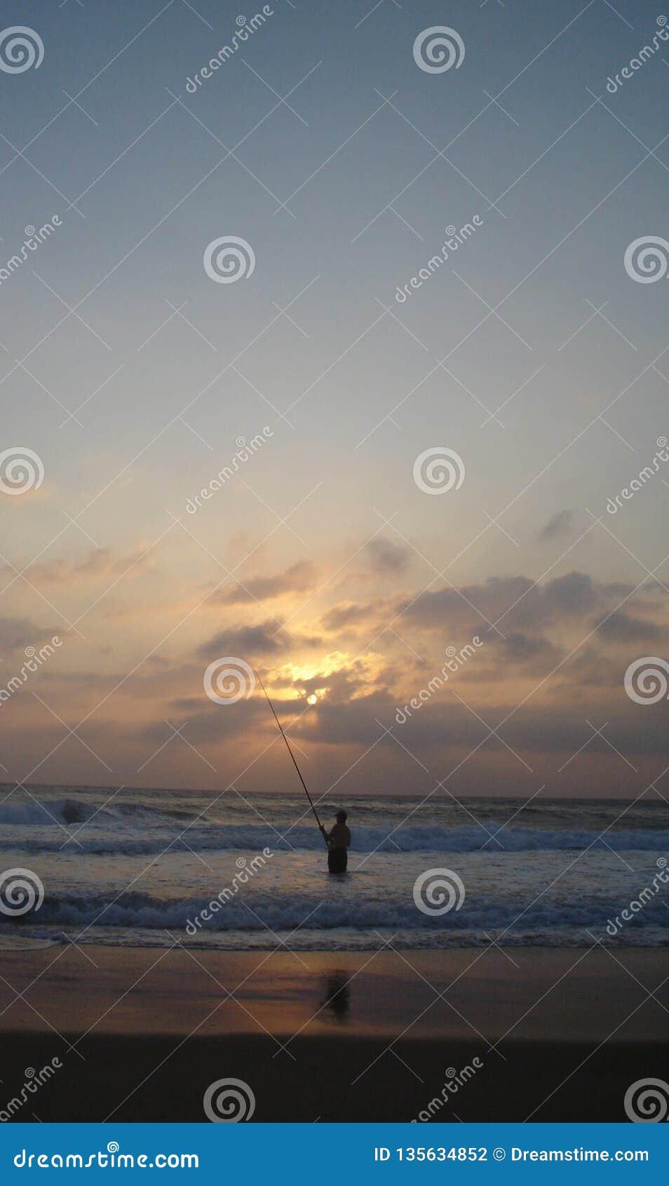 Eenzame geduldige visser die op vissen wachten om aas te nemen