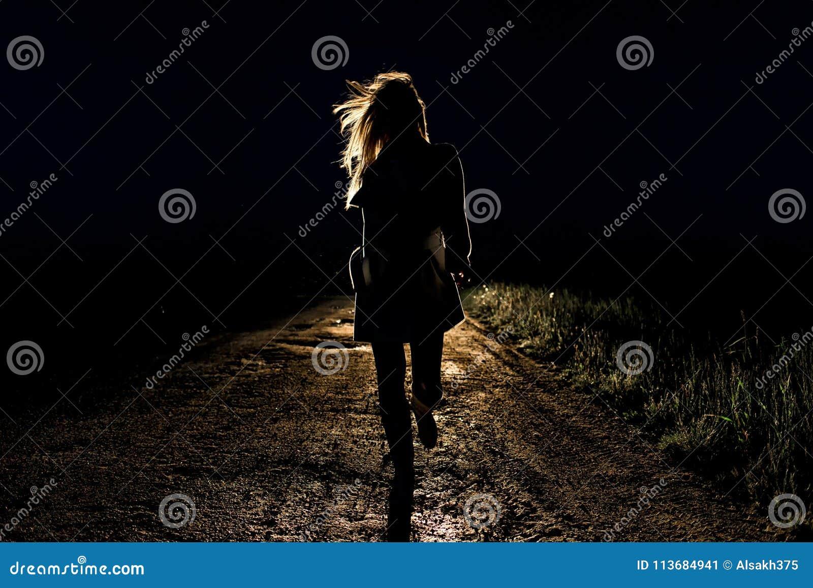 Eenzame jonge bang gemaakte vrouw op looppas van een de lege nachtweg weg in het licht van de koplampen van haar auto