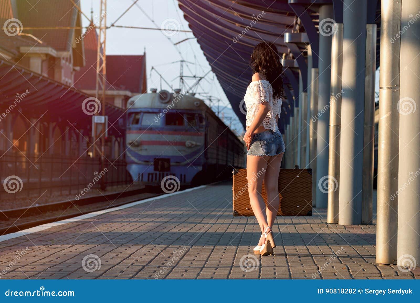 Eenzame jonge donkerbruine vrouw, in sexy borrels met oude koffer