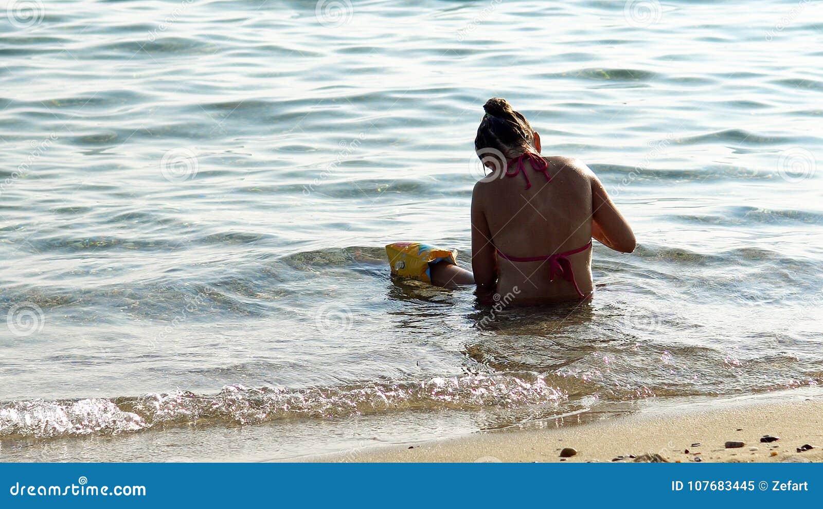 Eenzame meisjespelen alleen in overzees ondiep water