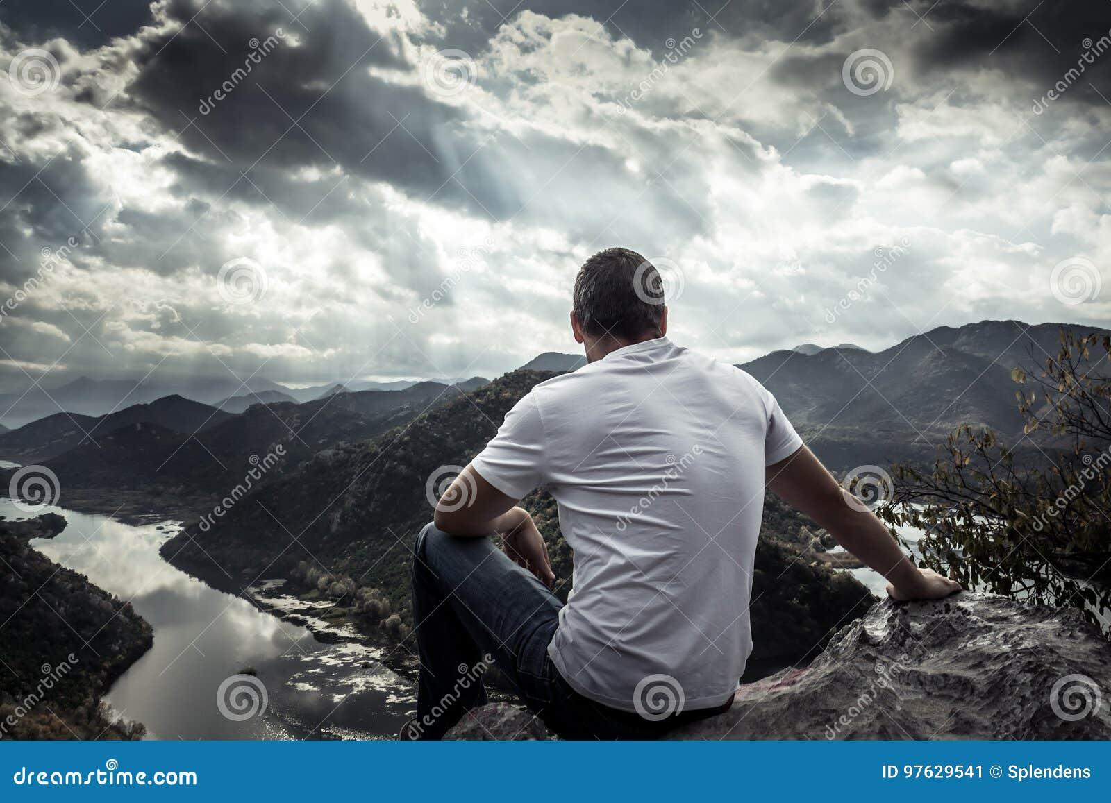 Eenzame mens die met hoop naar horizon op bergpiek met dramatisch zonlicht tijdens zonsondergang met effect van licht aan het ein