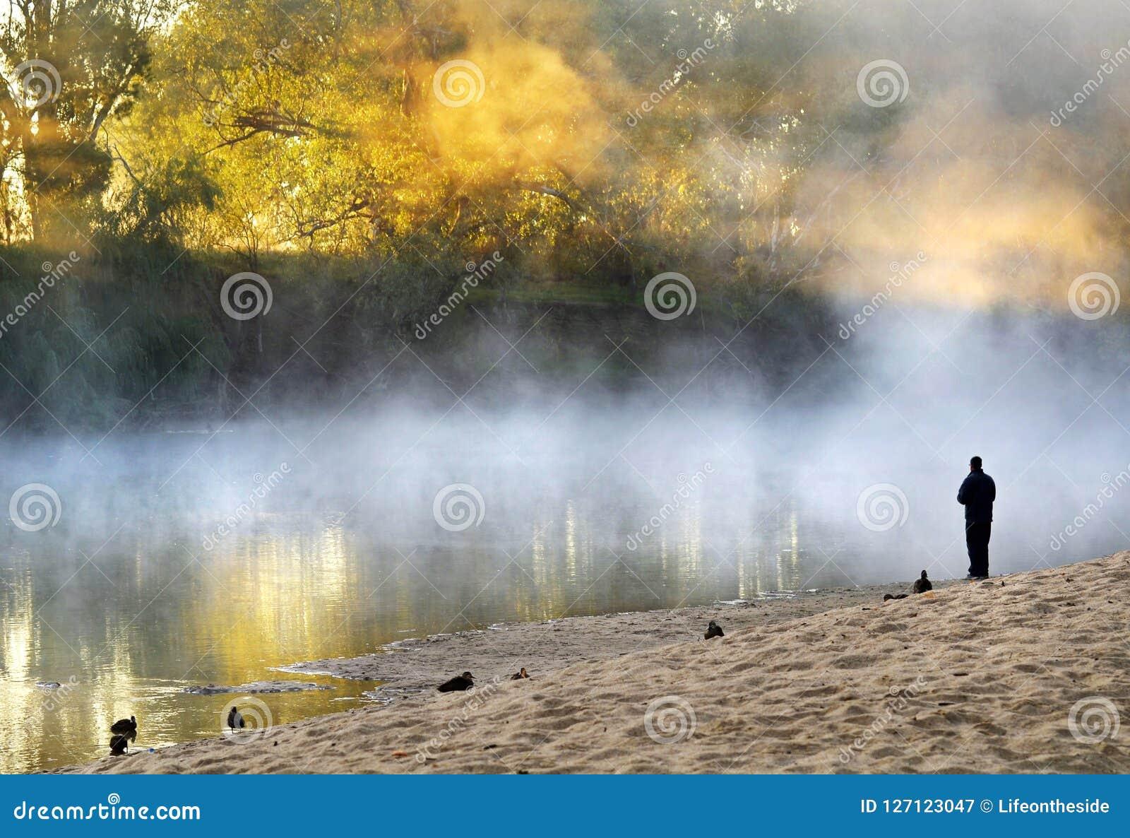 Eenzame mensen bevindende ziel die op bank mistige nevelige rivier zoeken