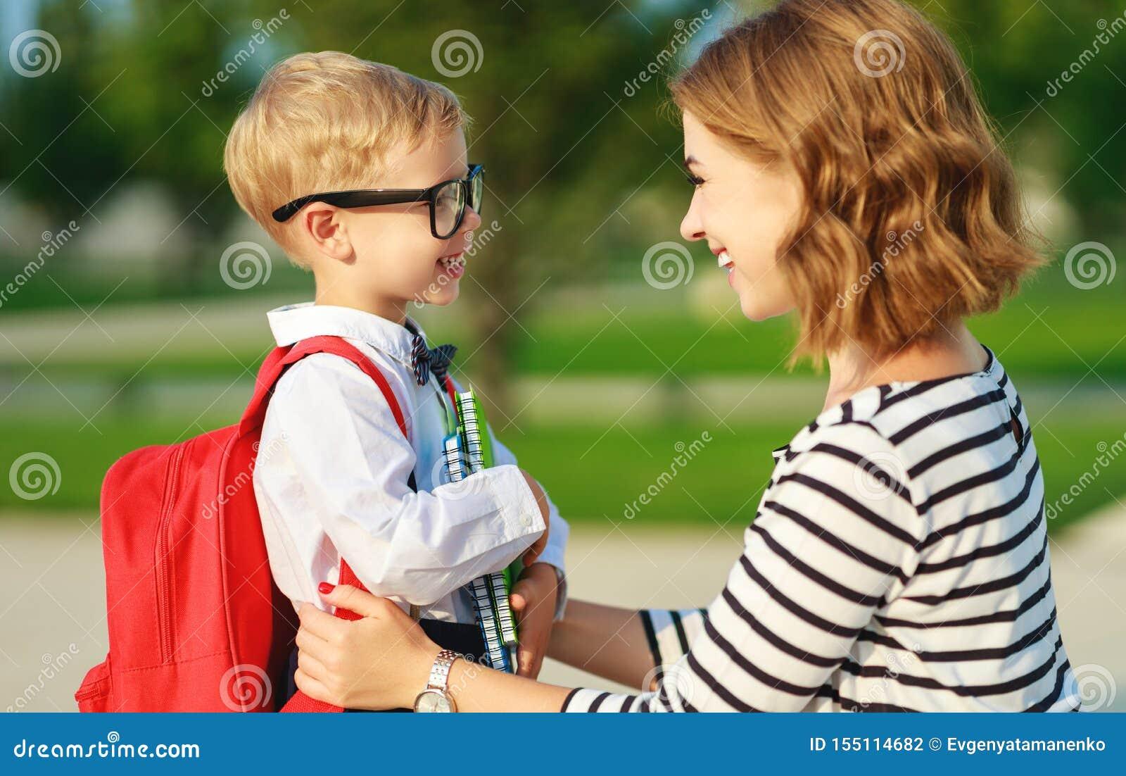 Eerste dag op school de moeder leidt weinig jongen van de kindschool in eerste rang