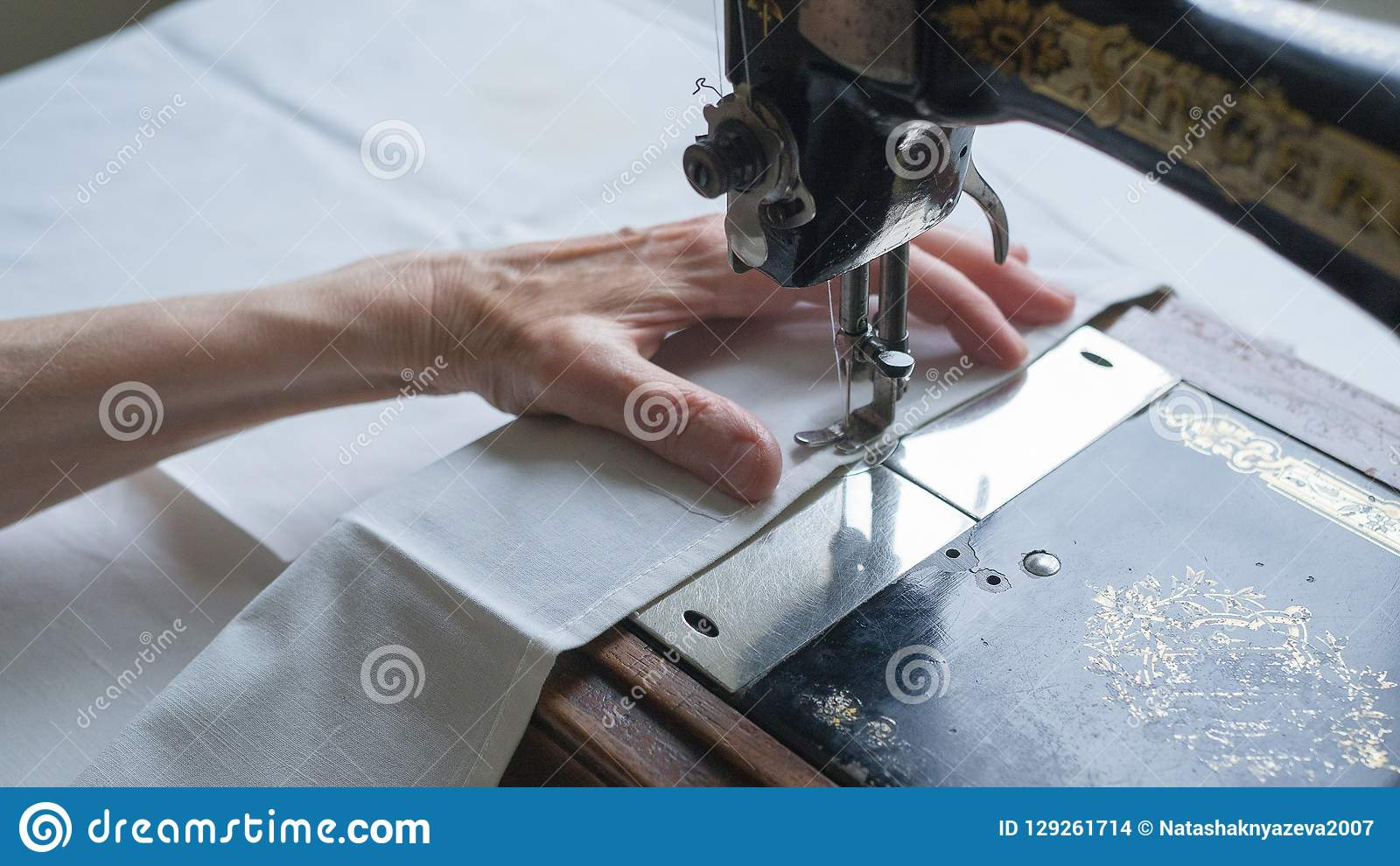 Eerste ZANGER naaimachine Het naaien Proces Voet van oude uitstekende naaimachine en handen van bejaarde selectief