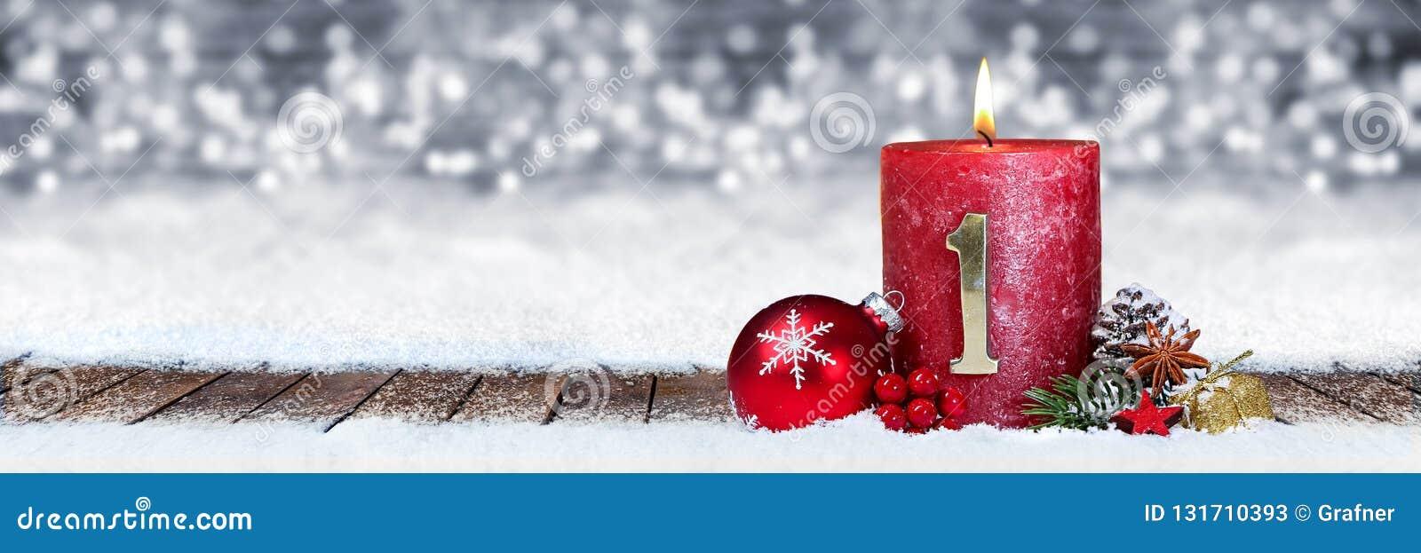 Eerste zondag van komst rode kaars met gouden metaalaantal op houten planken in sneeuwvoorzijde van panorama bokeh achtergrond