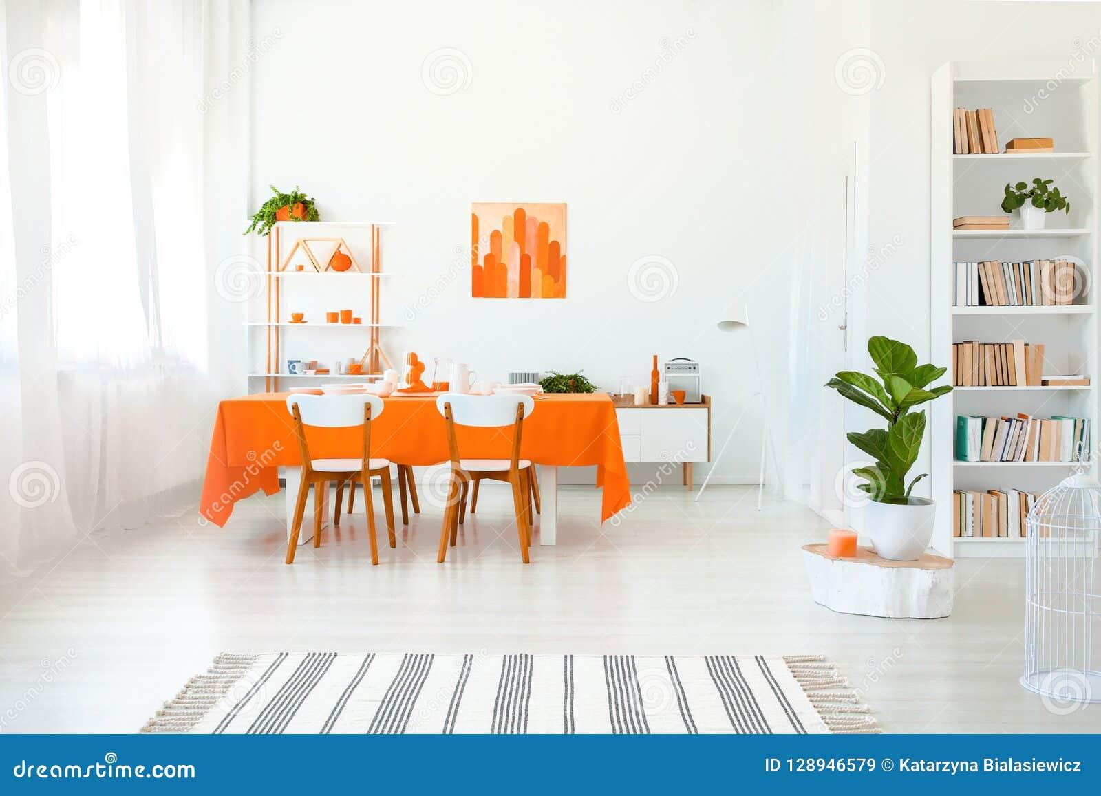 Eetkamer in levendige kleur Oranje tafelkleed op lijst met witte stoelen