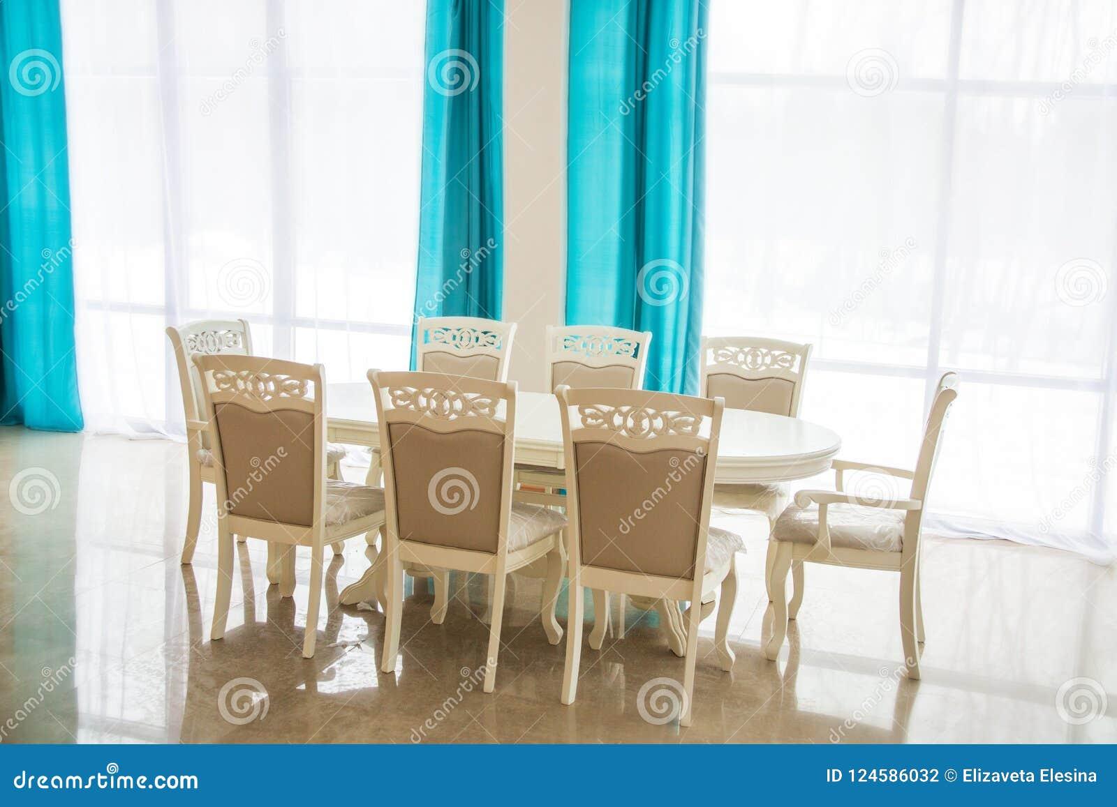 Eetkamer met houten lijst en stoelen helder binnenland vage