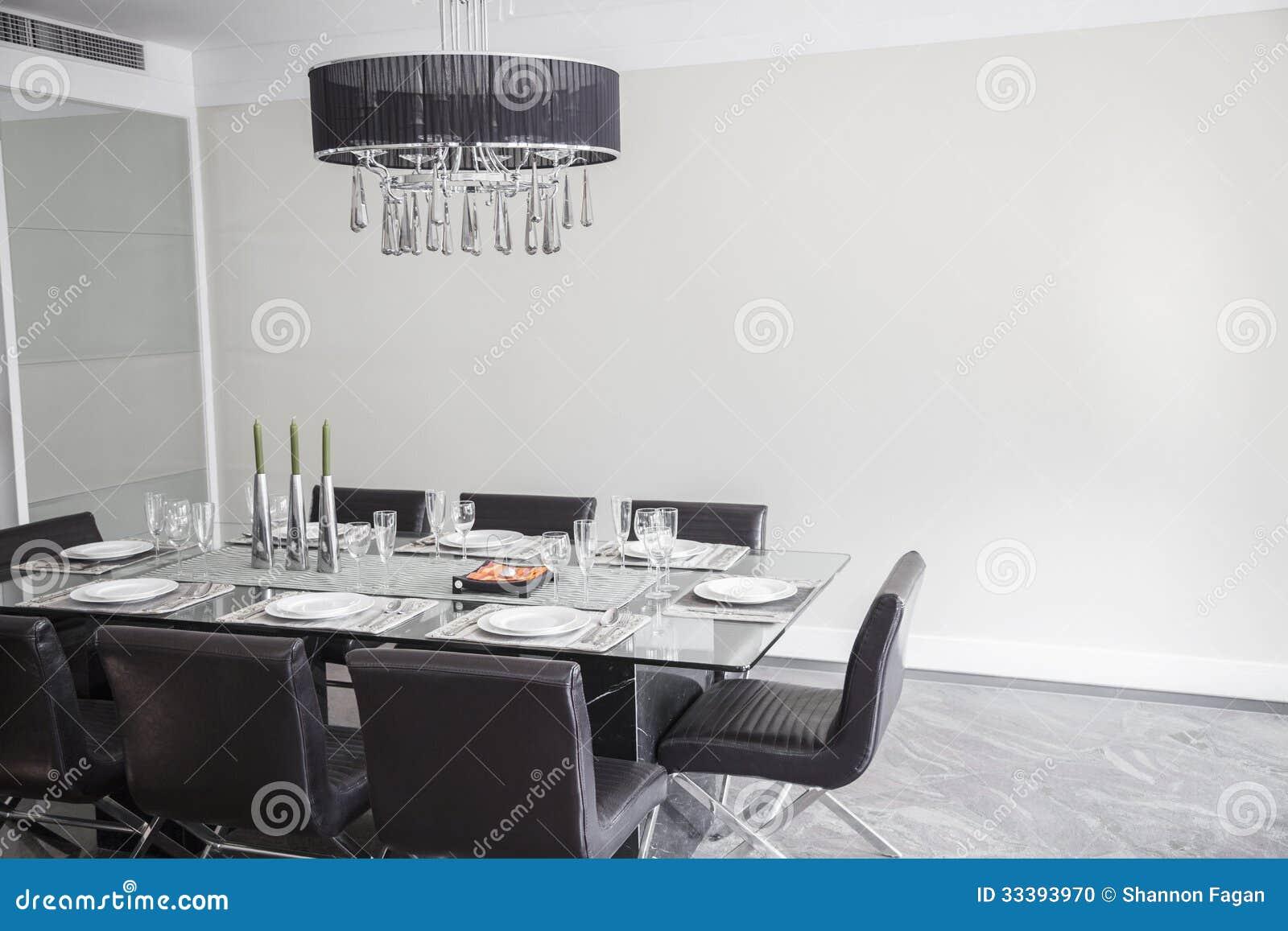 Eetkamer met moderne meubilair en kroonluchter stock foto