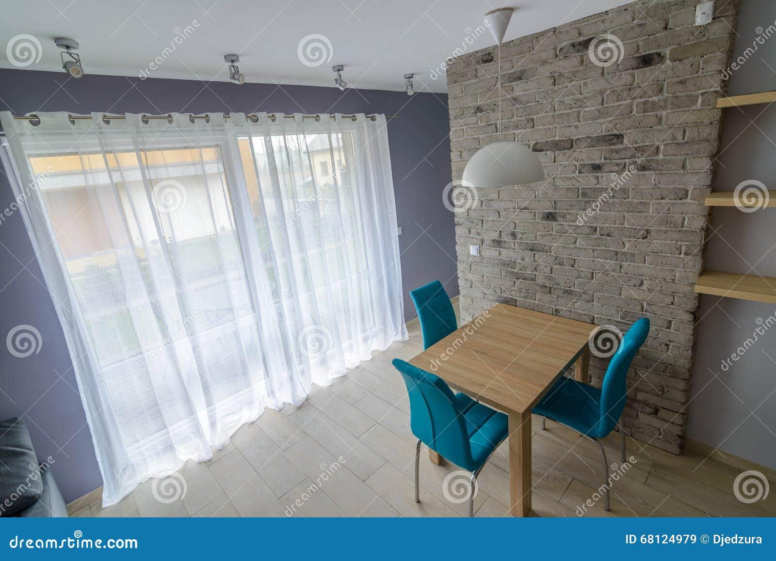 Eetkamer met oude grijze bakstenen muur stock afbeelding