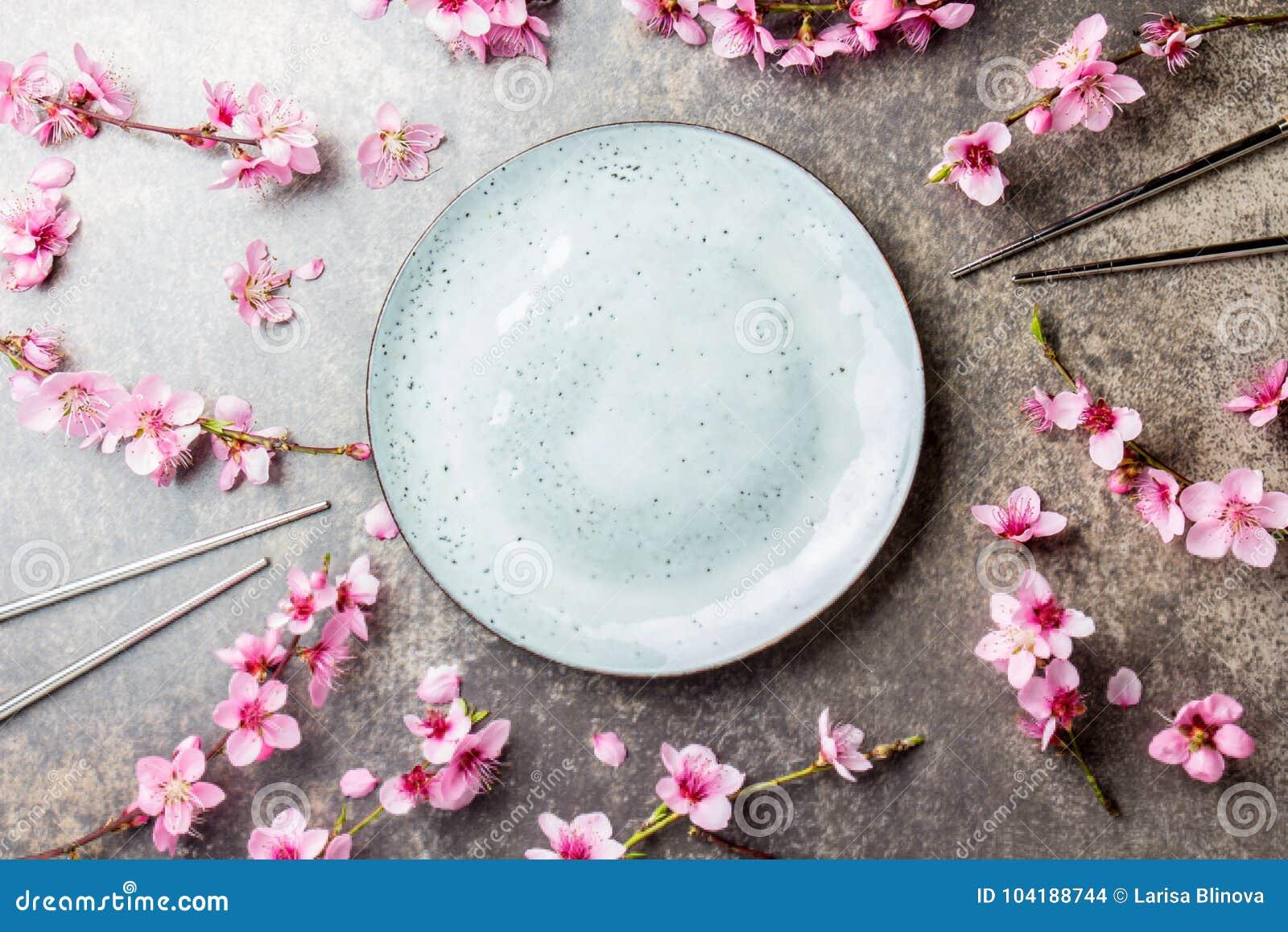 Eetstokjes en sakuratakken op grijze steenachtergrond Japans voedselconcept Hoogste mening, exemplaarruimte