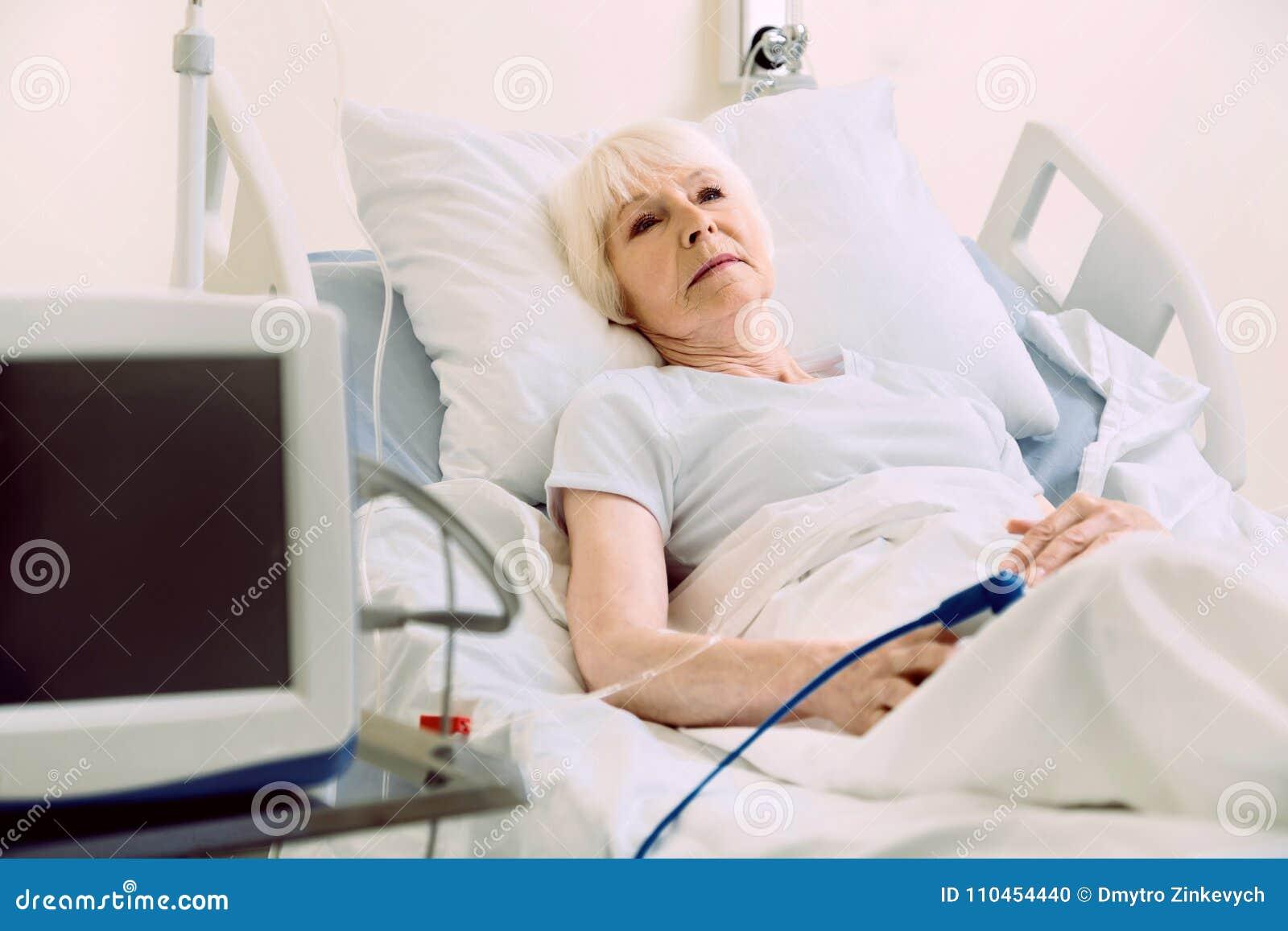 Eftertänksam kvinnlig patient som ligger i säng med pulsoximeteren