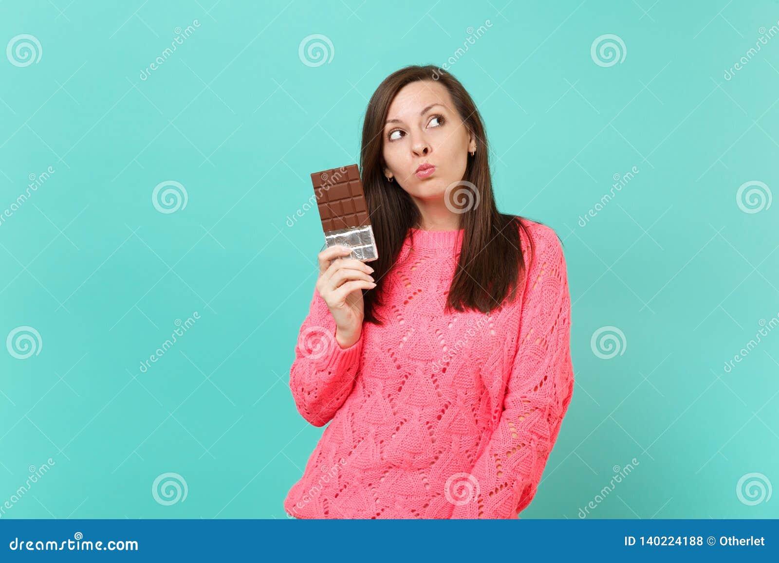 Eftertänksam nätt ung kvinna i den stack rosa tröjan som rymmer i handchokladstången som ser upp isolerad på blå turkos