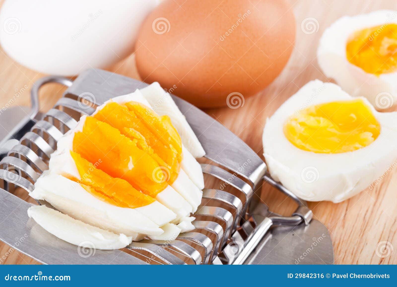 Cortador do ovo e ovos cutted na tabela