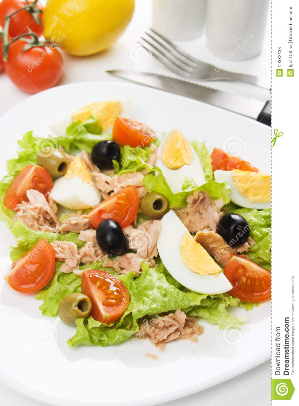 Hard boiled egg salad with tuna meat, tomato, lettuce and olives.