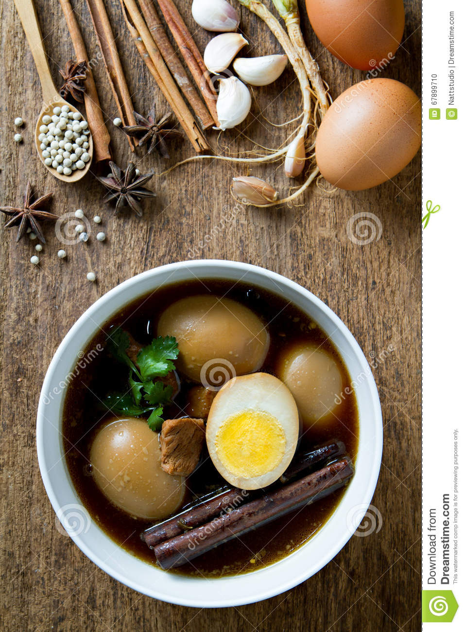 Eggs boiled in the gravy with spices on wooden background for 8 spices thai cuisine