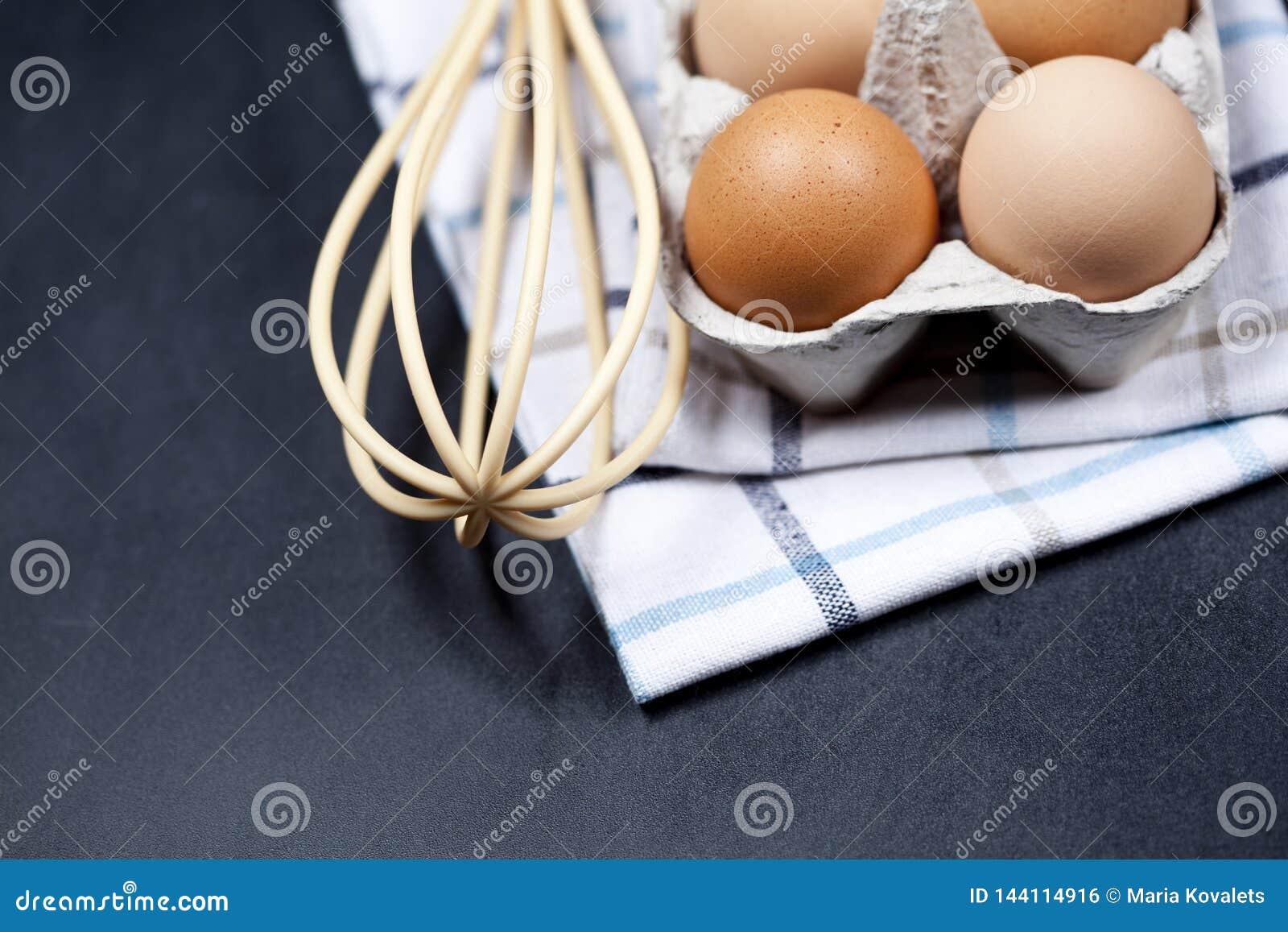 Eggs in cardboard box, towel and whisker closeup on backboard background