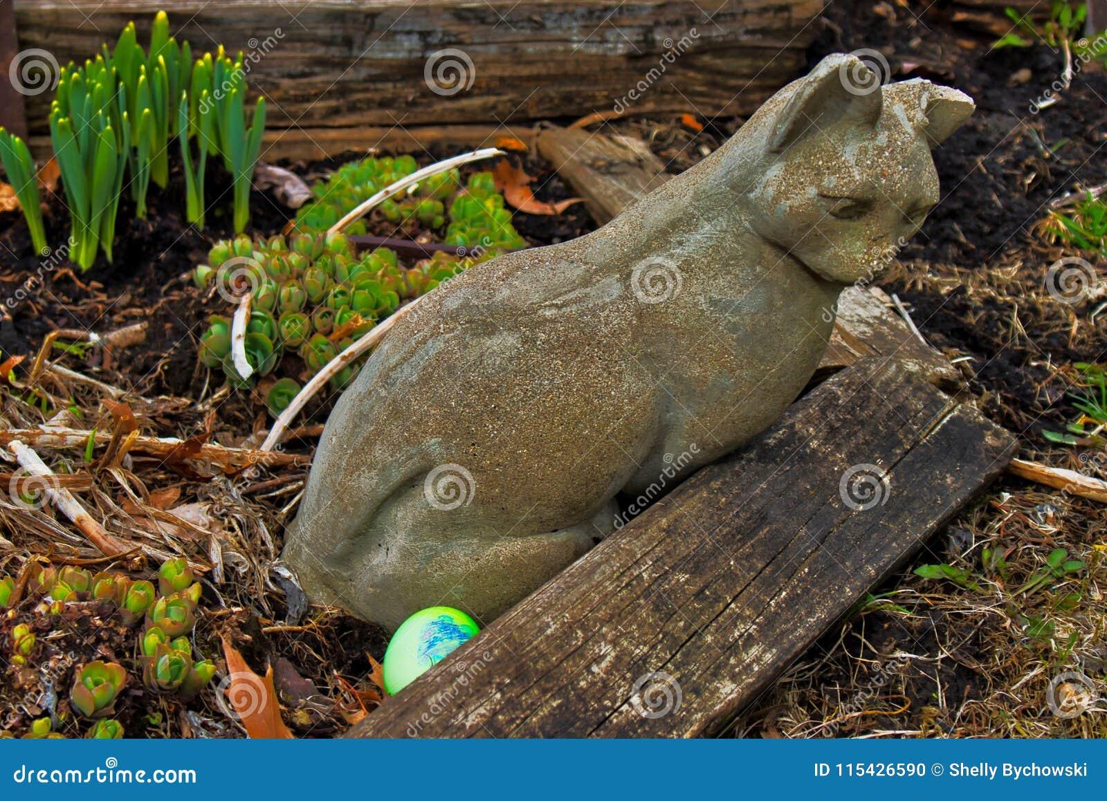 Eggs Hidden For Easter Egg Hunt Near A Garden Statue Of A Stone Cat ...