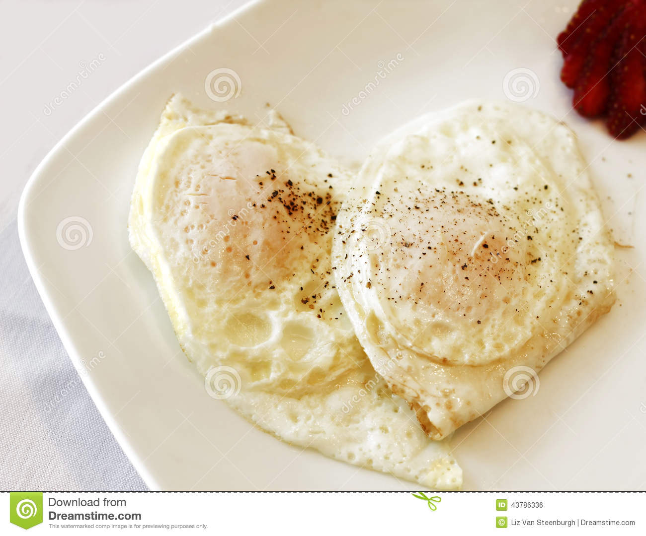 Two eggs cooked over easy, seasoned with pepper on a white plate.