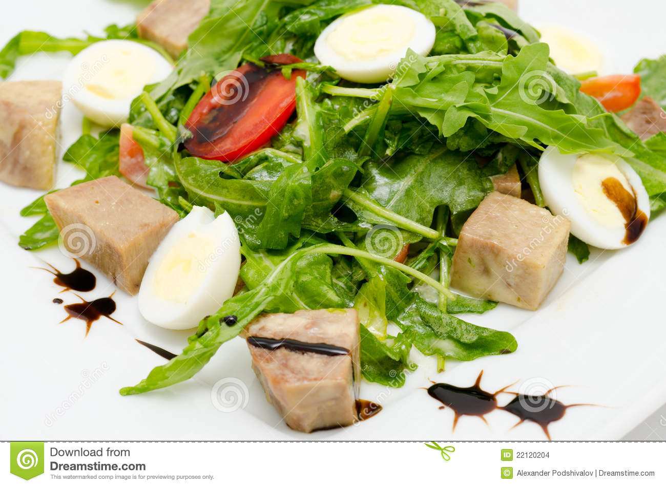 Salad - egg halves, pork cubes, roquette and tomatoes.