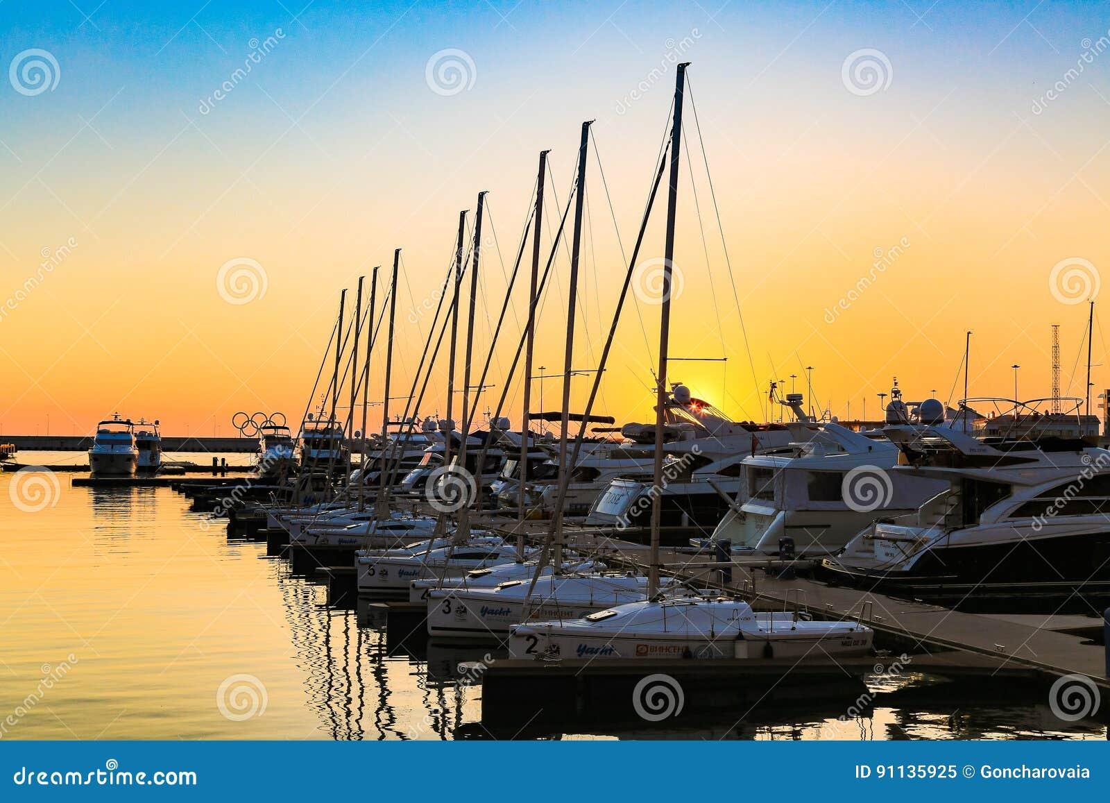 Żeglowanie łodzie i luksusowi jachty dokowali w porcie morskim w morzu przy zmierzchem