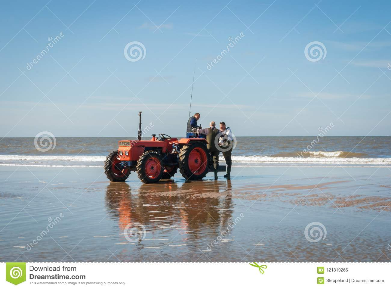 Egmond-aan-Zee, Netherlands - 2016-04-10: 3 men of the organisation with a red tractor on the beach