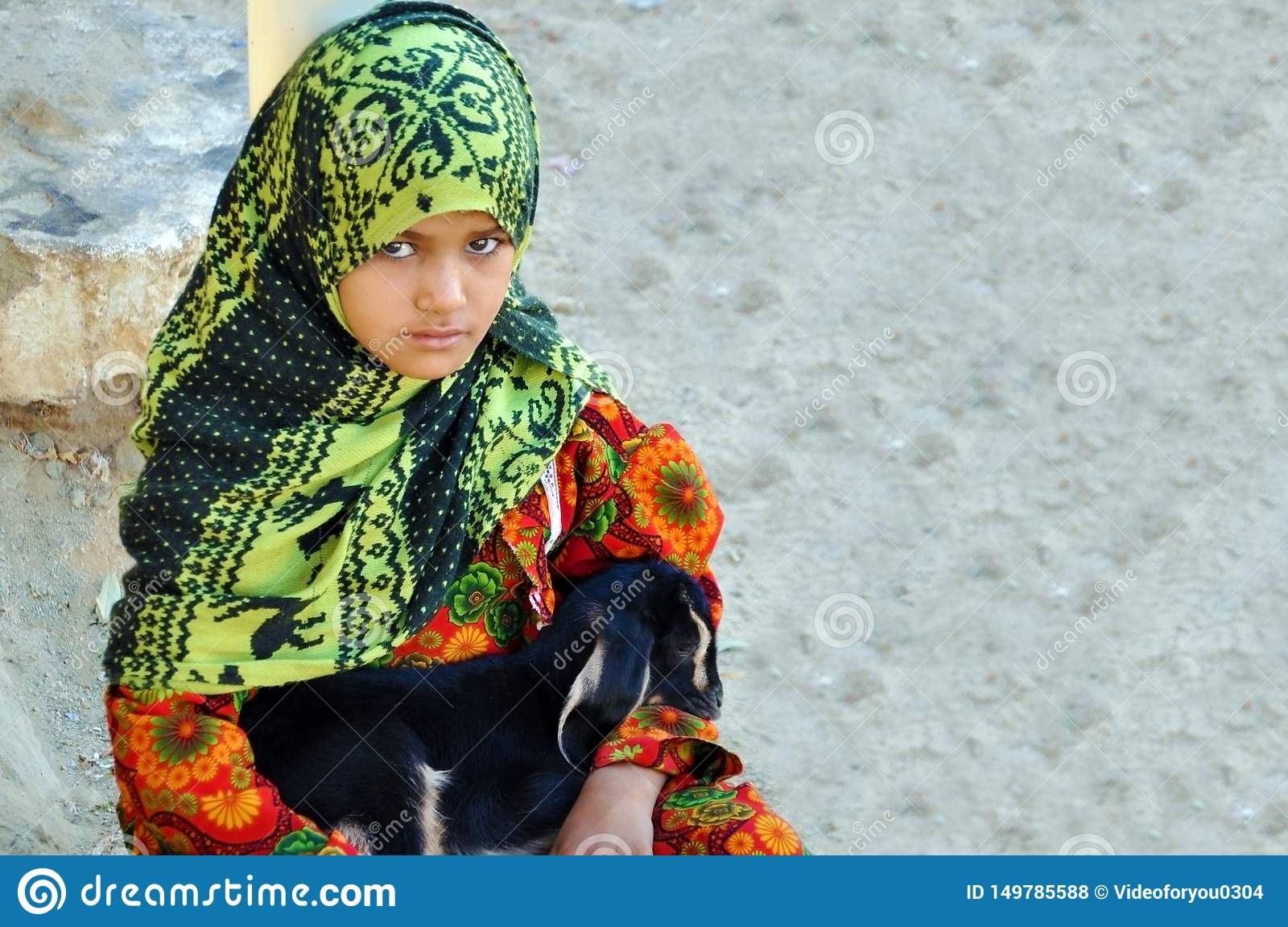 Egypt, October 22, 2012: A girl sits in a bright dress in a hijab with a baby goat in her arms