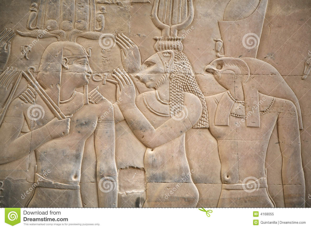 Wall with a relief of an egyptian scene with two gods an a king.