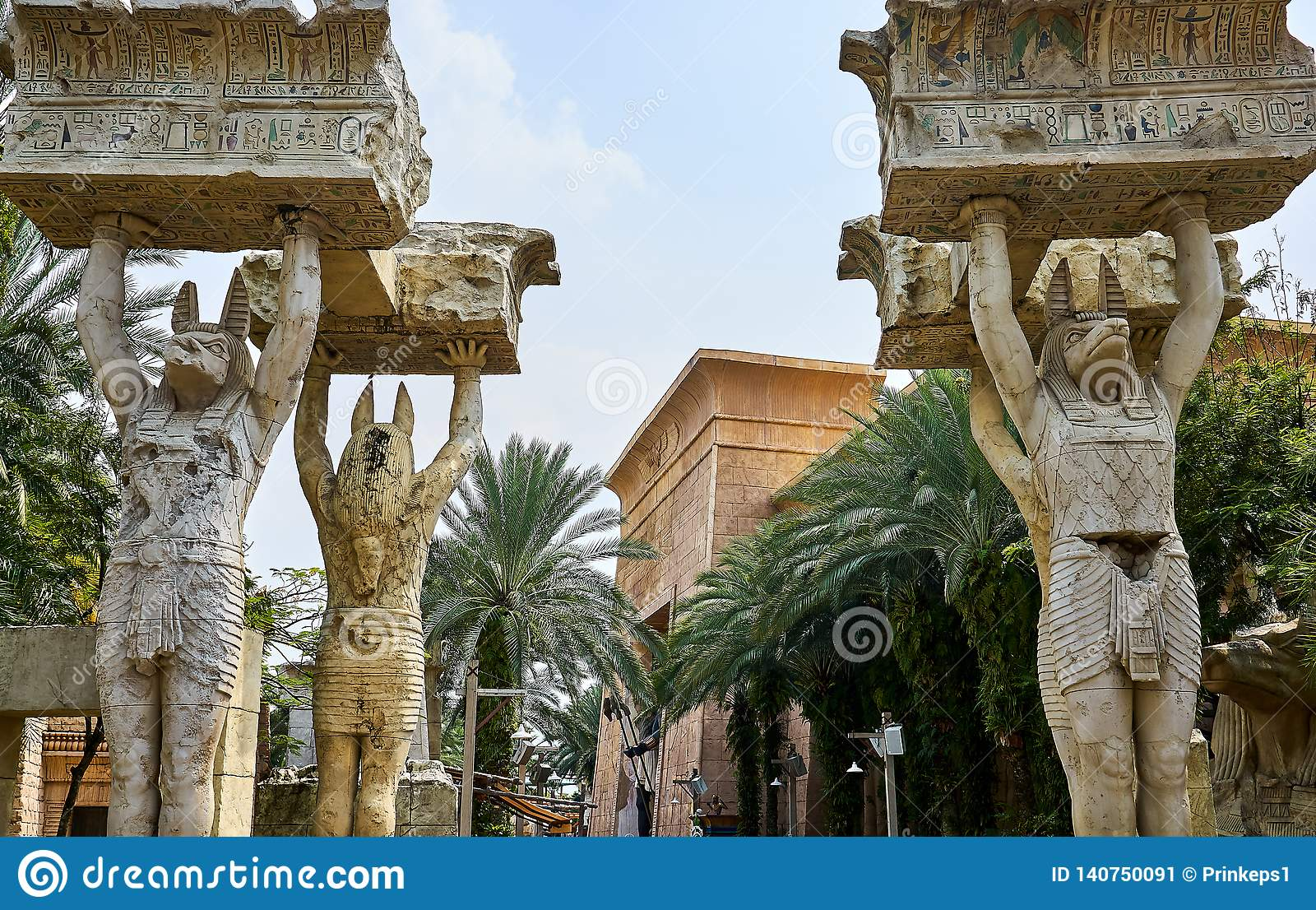 Egyptian statues lifting big boulders written with hieroglyphs at Unversal Studios Singapore
