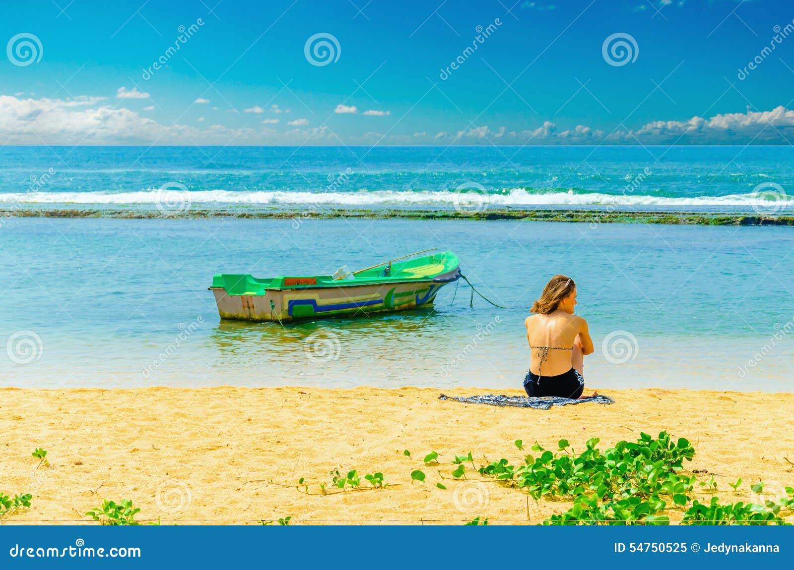 Egzota plaża, młoda dziewczyna, łódź rybacka i woda,
