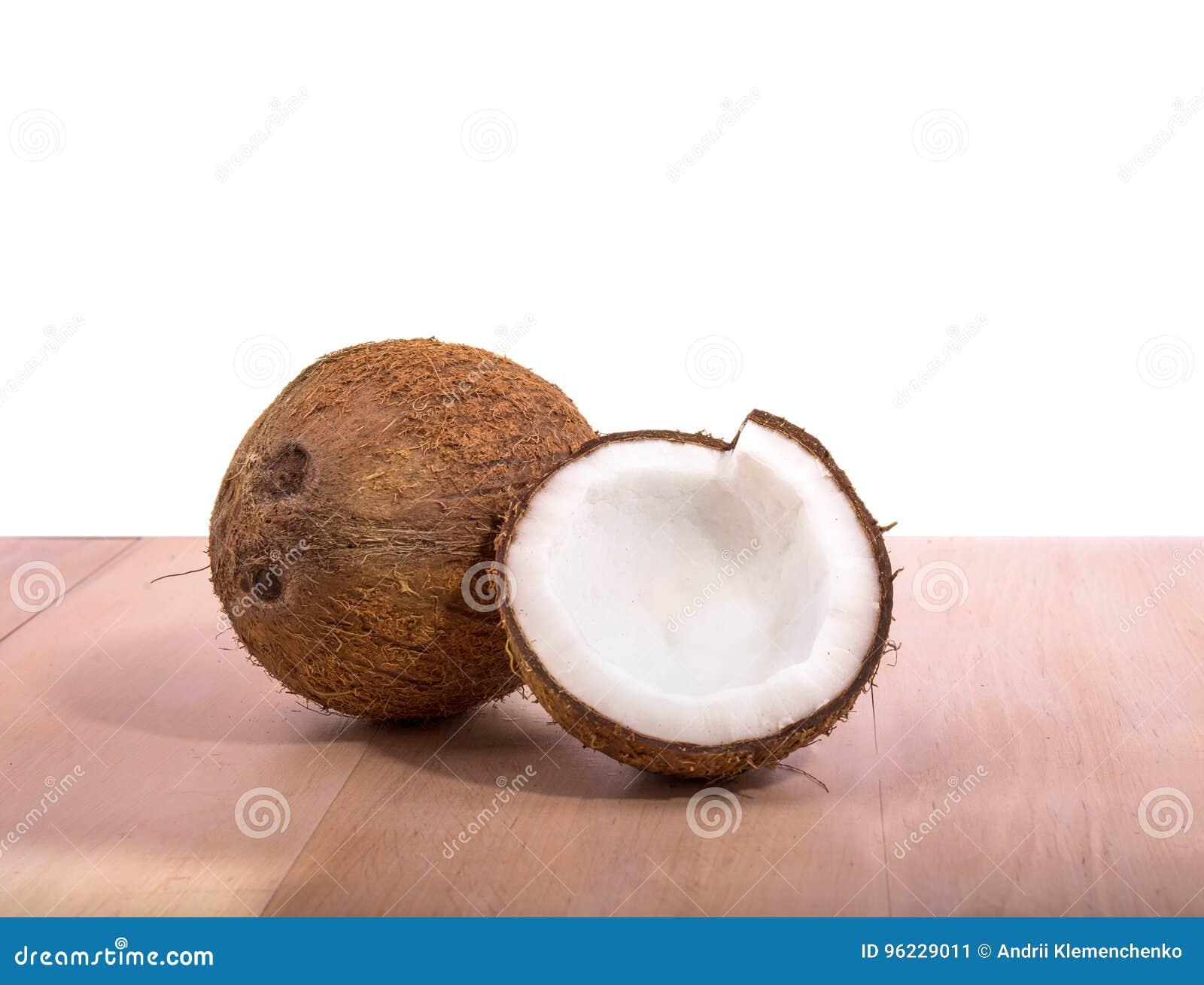 Egzotyczni i tropikalni koks na jasnobrązowym drewnianym stole na białym tle, Świeżość, natura, lata pojęcie