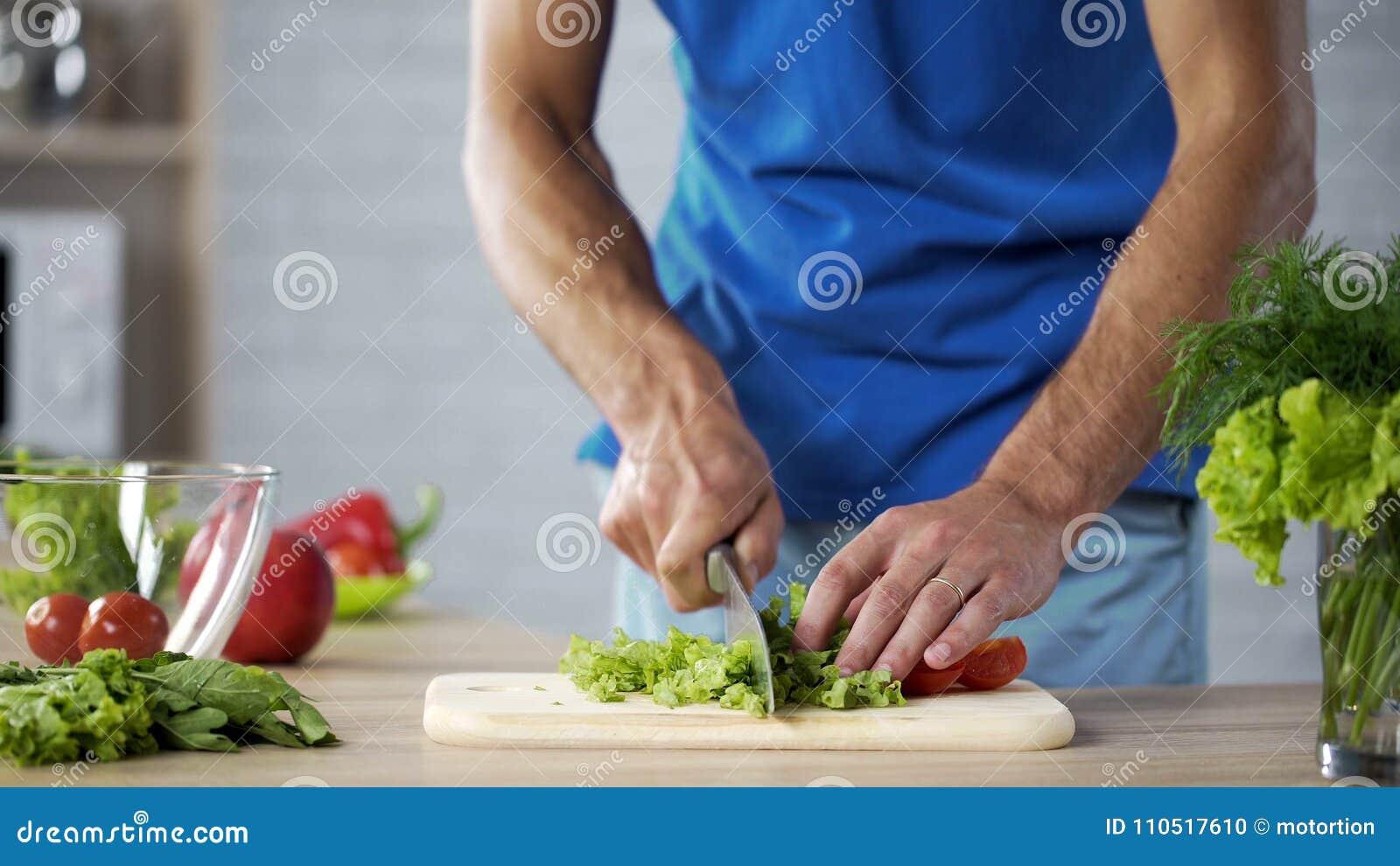 Ehemann, der an Bord frischen Salat für das gesunde Familienmittagessen, Hilfe kochend schneidet