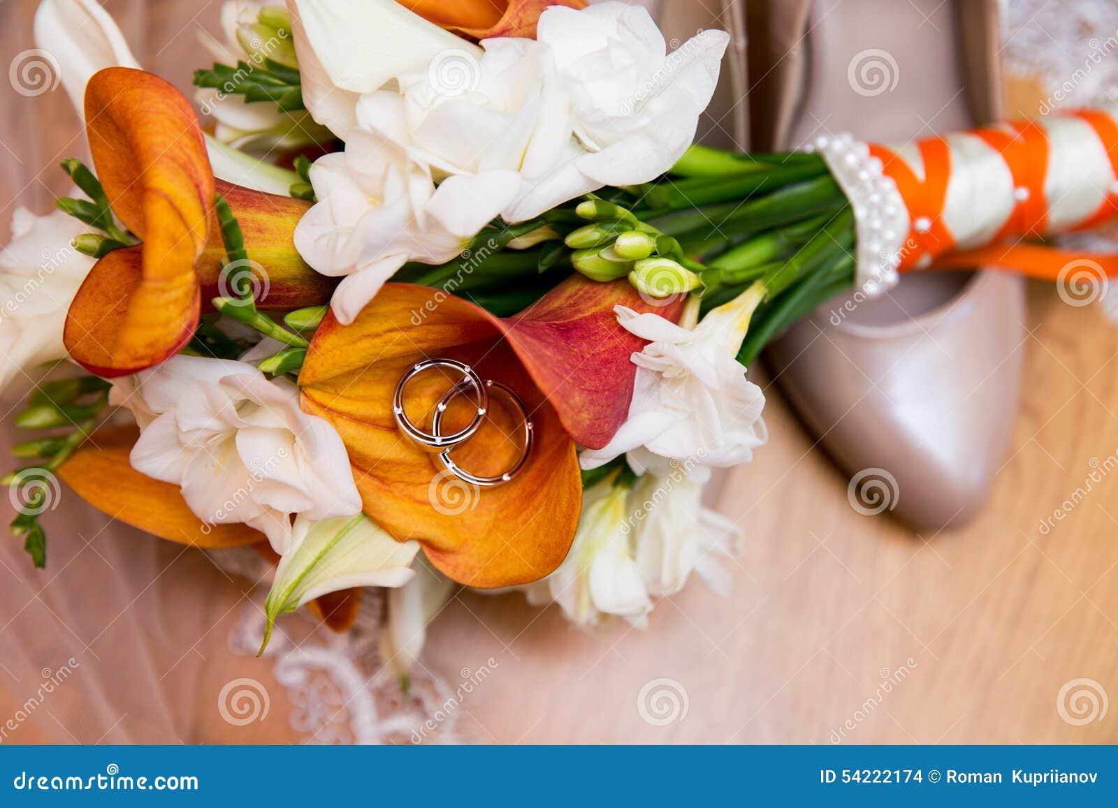 Eheringe mit Blumenstrauß und Schuhen