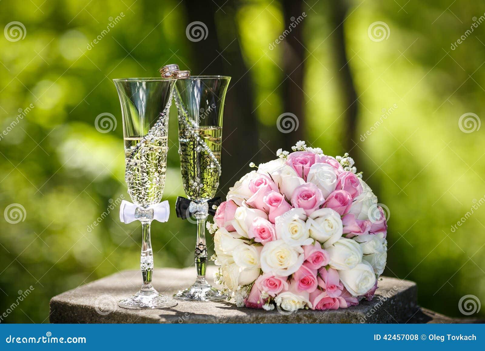 Eheringe mit Rosen und Gläsern Champagner