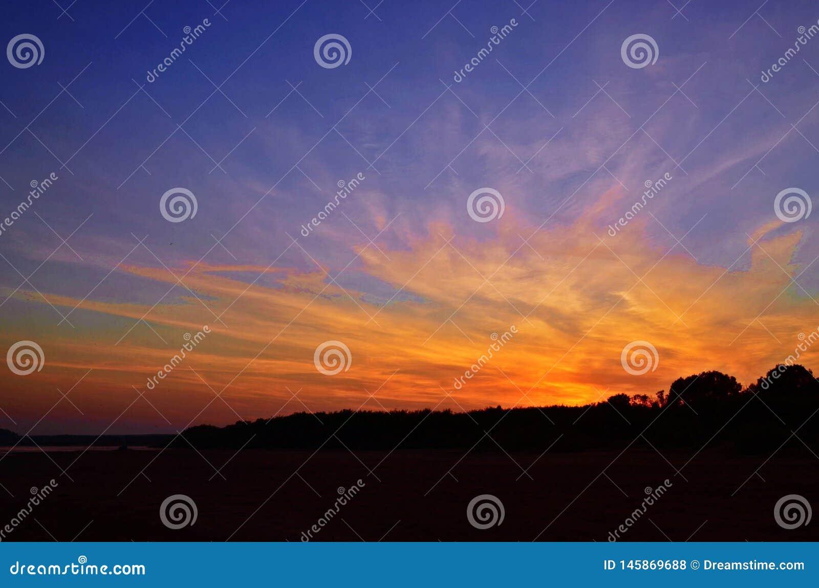 Ehrfürchtiger Schuss von den brennenden Wolken wegen der Strahlen der Sonne bei Sonnenuntergang