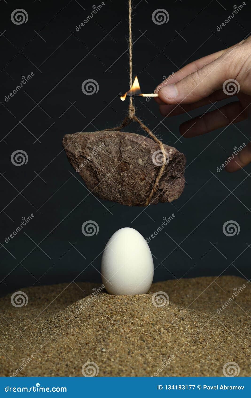 Ei onder een steen die op een kabel hangen