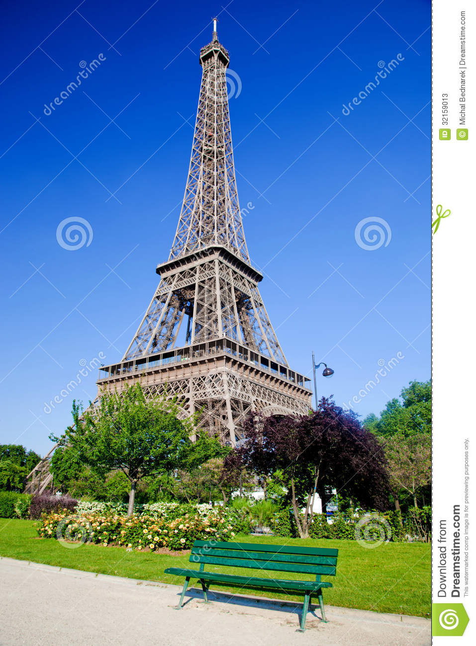 Eiffel Tower surrounded by the park with a bench, trees and flowers ...