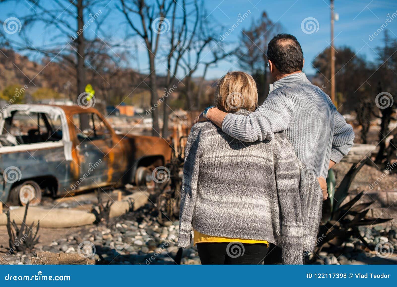 Eigenaars, die gebrand en geruïneerd huis en werf na brand controleren