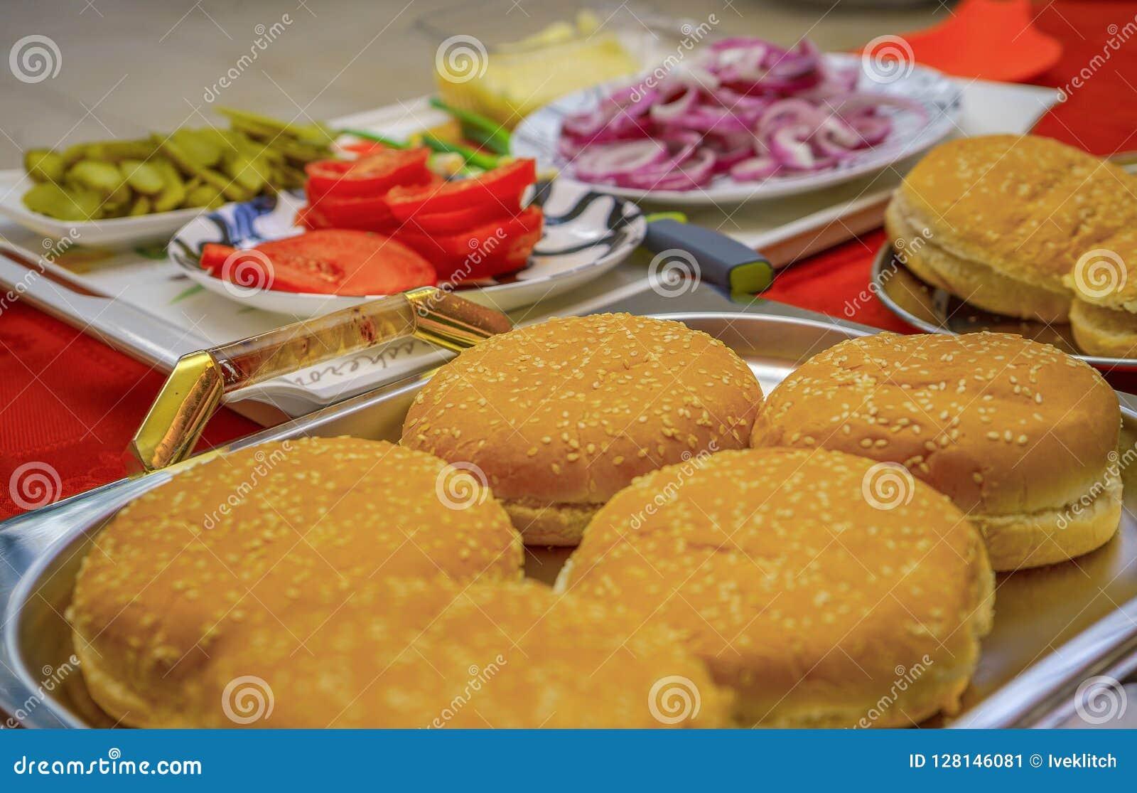 Eigengemaakte die hamburgeringrediënten op dienblad en platen in openlucht worden geschikt Ui, gezouten komkommers, kersentomaten