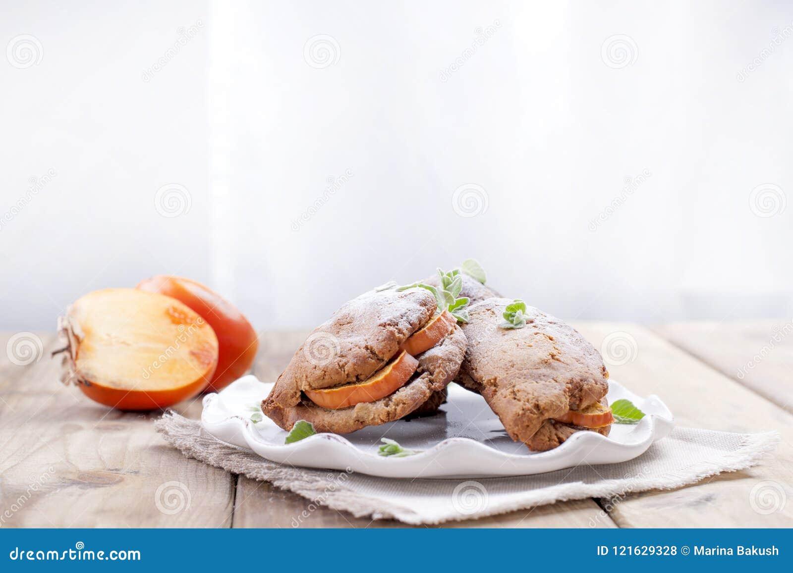 Eigengemaakte gebakjes met verse dadelpruimen, voor ontbijt, witte plaat op een servet Houten lijst Vrije Ruimte voor Tekst of Re
