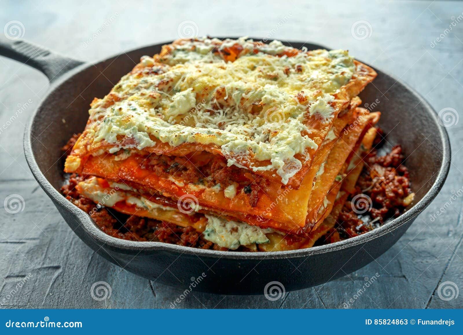 Eigengemaakte Knapperige lasagna s in ijzerpan met fijngehakte rundvlees bolognese saus, parmezaanse kaaskaas