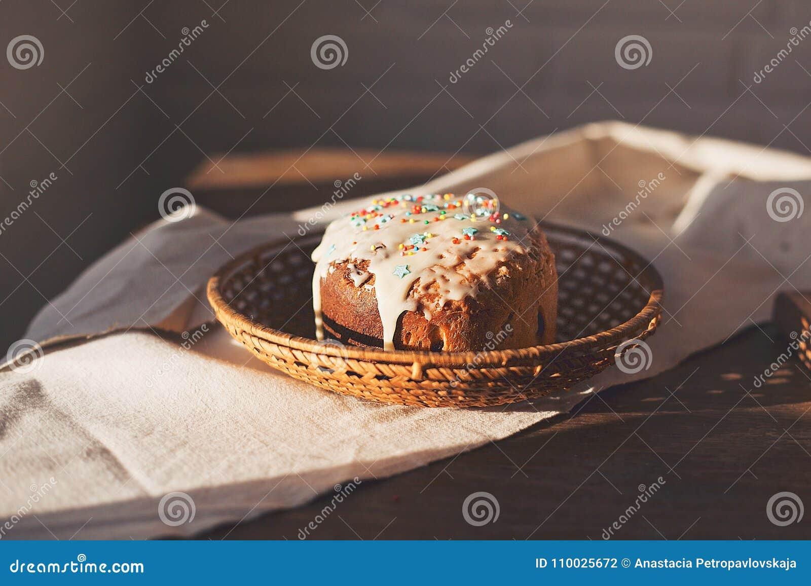 Eigengemaakte Pasen-cake kulich op lijst verfraaid wit suikerglazuur, mooi zonsonderganglicht