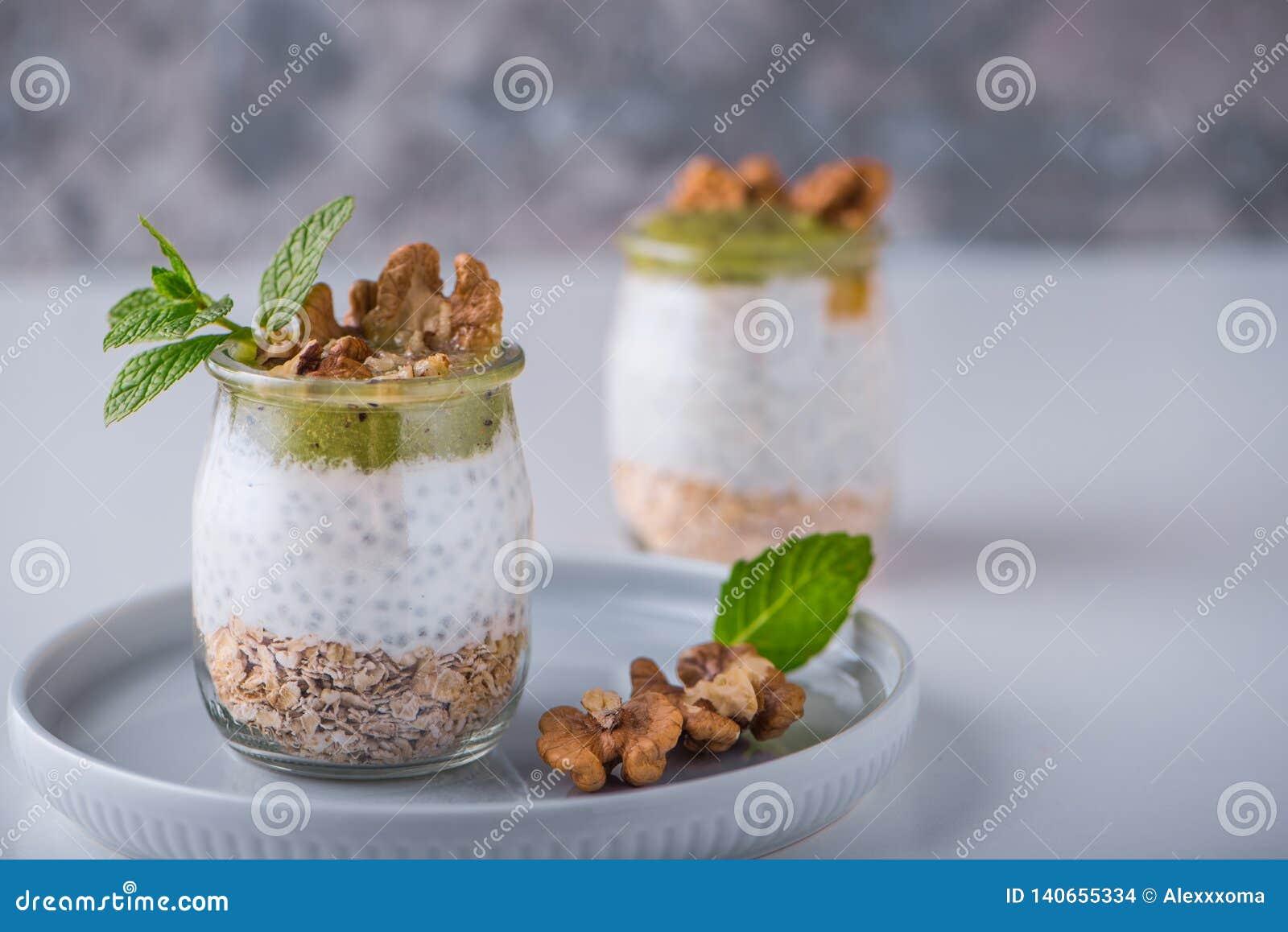 Eigengemaakte pudding van Chia-zaden en amandelmelk met graangewassen en puree van kiwi met okkernoten en munt in glaskruiken Gez