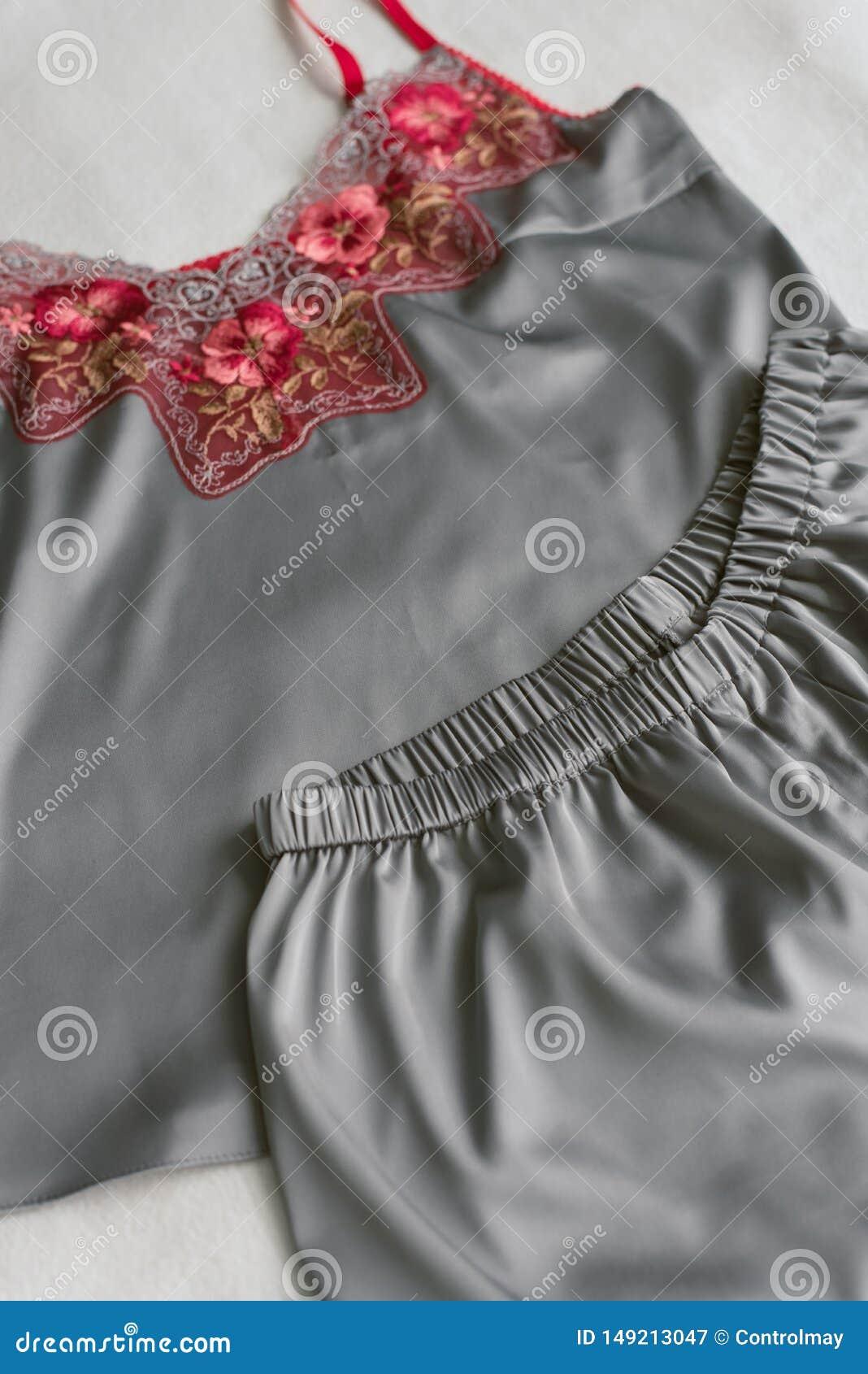 Eigengemaakte zijdepyjama s die op het bed zonder iedereen liggen grijze pyjama s met rood kant op een beige achtergrond