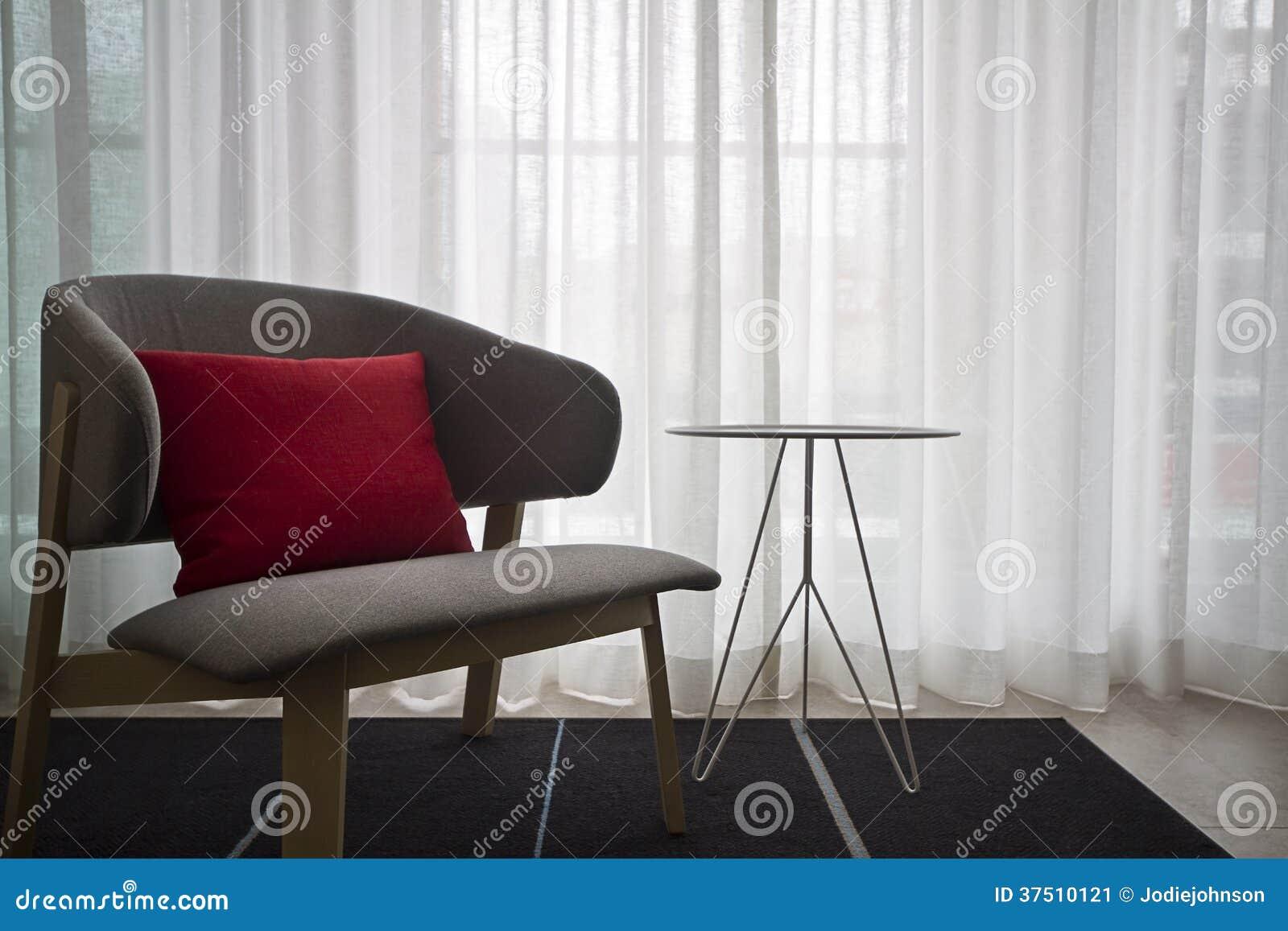 Eigentijdse binnenlandse grijze stoel zuivere gordijnen stock