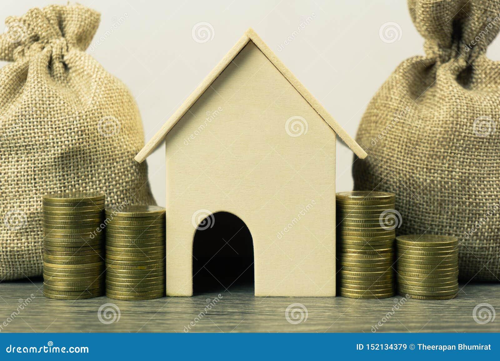 Eigentums-Investition, Wohnungsbaudarlehen, Haushypothekenkonzept Ein Modell des kleinen Hauses mit Stapel von Münzen und von Gel