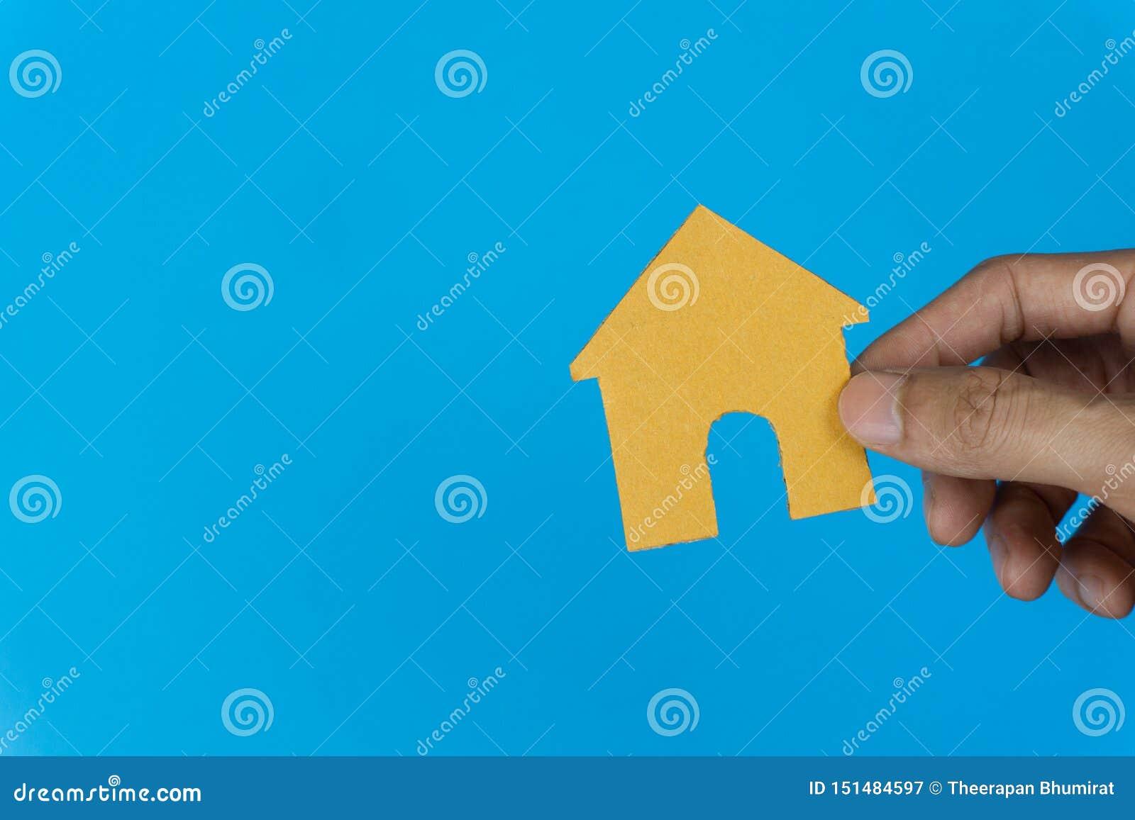 Eigentums-Konzept Wohnungsbaudarlehen, Rückhypothek, Wohnung, Geschäft und Finanzierung Eine Mannhand, die kleines Haus auf blaue