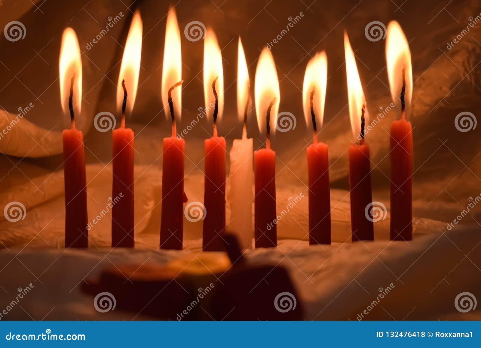 Hanukkah candles lit in the dark